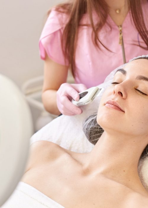 Beautiful woman receiving ultrasound facial peeling. Skin cleansing procedure at beauty spa salon. Cosmetologist makes cleansing treatment for her young client via moder equipment. Skin care concept.