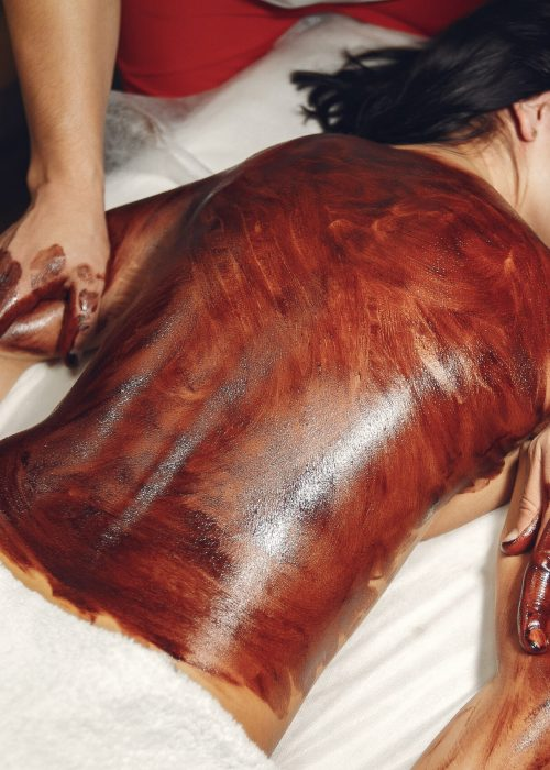 Massage doctor. The man make a masahe for woman. Procedures with chocolate